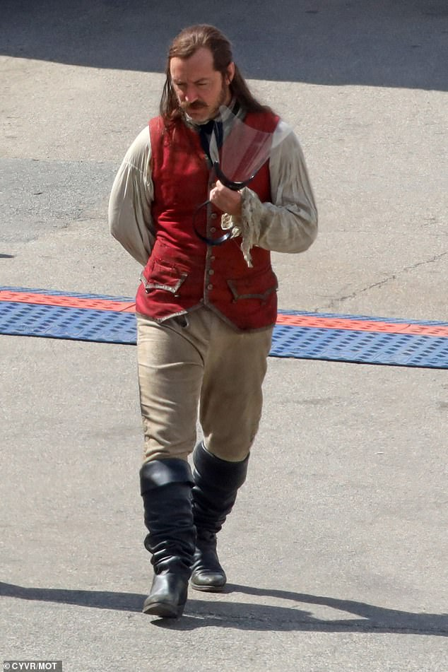 Eye-catching: Dressed in a red waistcoat and black boots, Jude was the captain at the slant loop at all times as he made his way to the set for the shoot