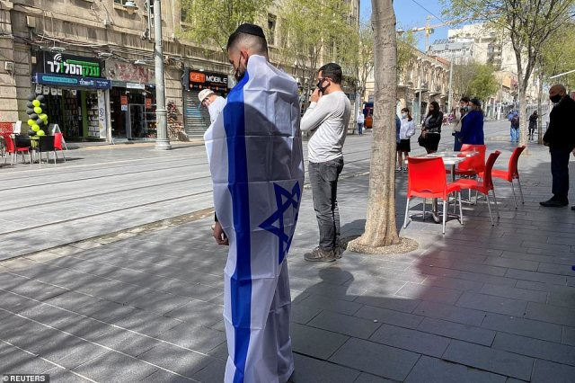 A man covered in an Israeli flag stands still as a two-minute siren marking the annual Israeli Holocaust Remembrance Day is heard in Jerusalem April 8, 2021. The day marks the anniversary of the 1943 Warsaw Ghetto uprising - the most significant act of Jewish resistance against Nazi Germany during the Holocaust