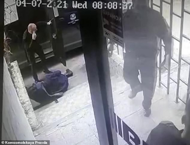 But the guard 'accidentally pulled the trigger', according to reports, and killed Korobjov (left on the floor). Pictured: Another man (left) is seen gesticulating in horror at the shooter, who was later detained
