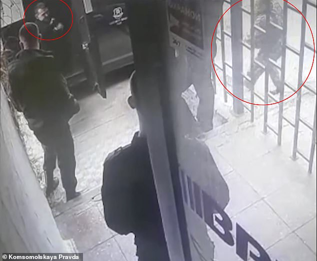 Oleg Korobkov, 23, (left) posed as a robber during a drill in Russian city Nizhny Novgorod as his colleagues - including a guard (right) - were ordered to role play responding to an attack.
