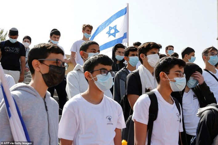 Students and teachers of Bar Ilan School stand in silence in the Israeli city of Netanya on April 08, 2021, as sirens blare across Israel honouring the six million Jews killed by the Nazis during World War Two