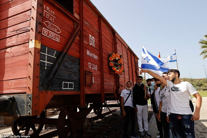 Students and teachers of Bar Ilan School visit an authentic German train, that transported Jews to extermination camps, on the Holocaust Remembrance Day in the Israeli city of Netanya on April 8, 2021