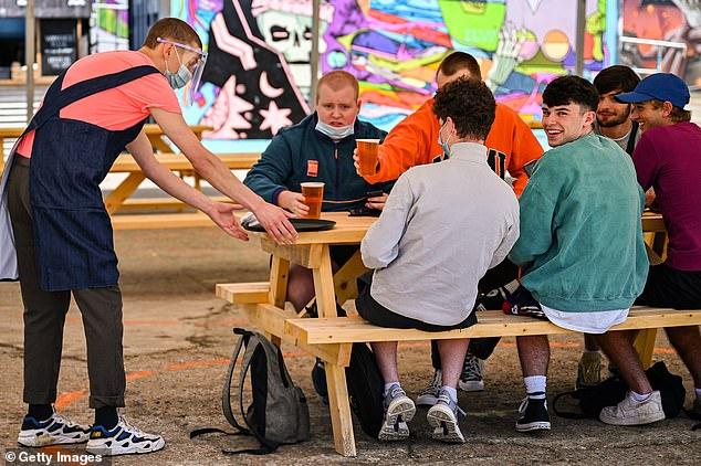 Punters enjoy a drink together in a pub garden in Glasgow, Scotland, last summer