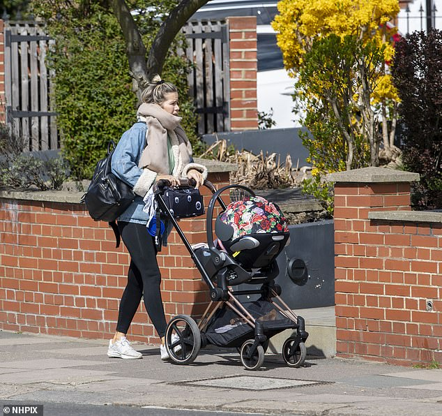 Golden girl: The new mum looked stylish as she wore her blonde tresses in a half-up-half-down hairstyle, which she tied with a cute black scrunchie