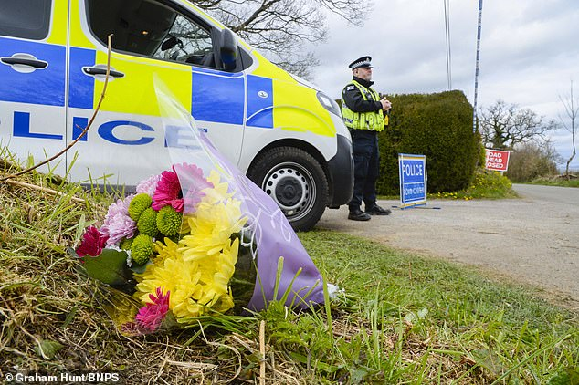 The property is a large detached home in a tiny hamlet, near Gillingham, Dorset. Pictured: Flowers left at the scene today, as police continue their investigation