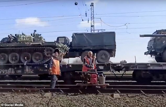 Railway workers on the line as tanks and trucks are transported close to Russia's border with Ukraine
