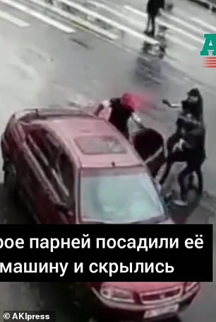 Man with a red cap opens the car door as Karanthbekova is pushed inside