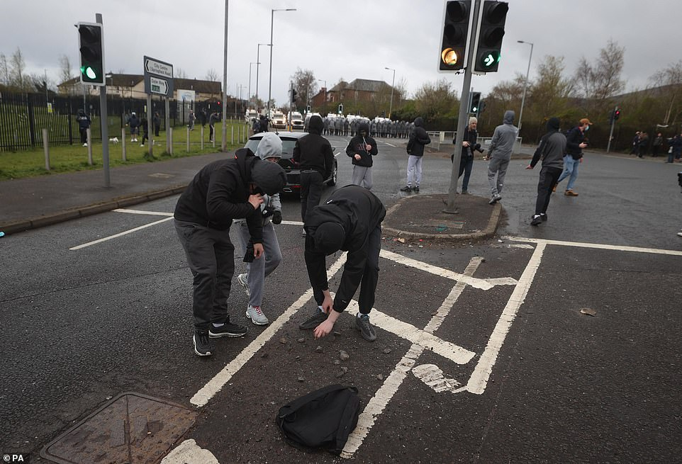 Youths pick up stones to throw at PSNI officers on the Springfield road, during further unrest in Belfast. The cause of the unrest has been attributed to frustration over a decision not to prosecute members of Sinn Fein over alleged coronavirus regulation breaches at the funeral of republican Bobby Storey