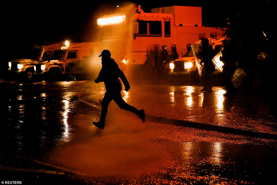 A rioter reacts as the police use a water cannon in Belfast amid clashes between officers and youths