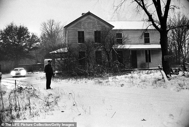 Deputy sheriff standing outside of house belonging to alleged serial killer Ed Gein, where he lived a deceptively quiet life and where parts of his victim's bodies were found