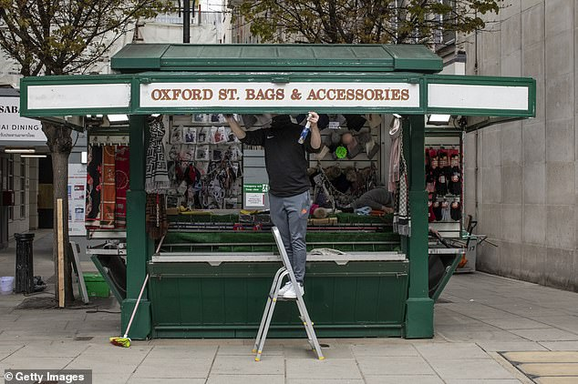 A stall holder prepares his stand yesterday ahead of the shops around it to reopen next week on Oxford Street in London