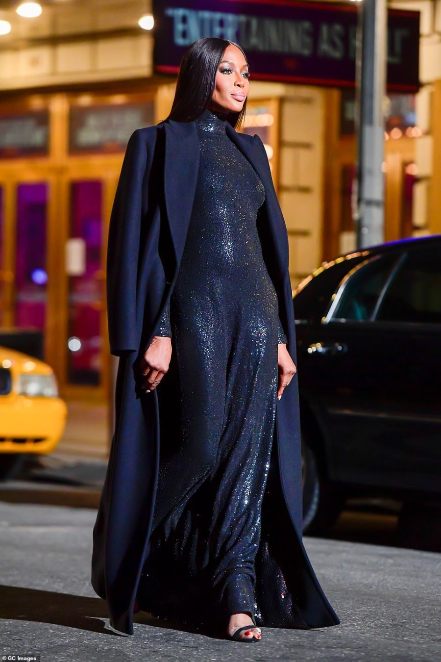 Conservative: The outfit reached all the way up to her chin and down to the ground and featured long sleeves. She wore it with a large black overcoat