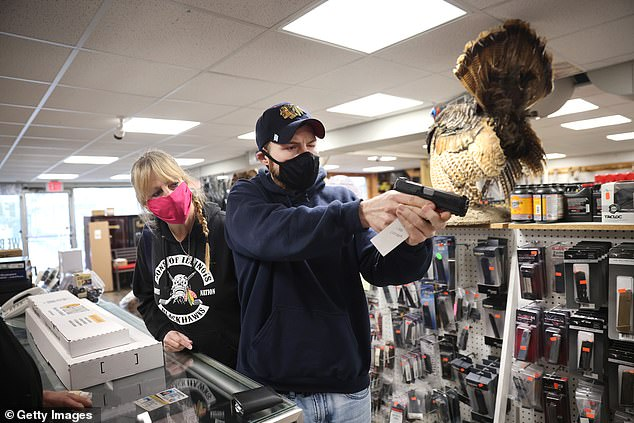 Alexander Carey (right), accompanied by his mother Rosalie, shops for a new handgun at Freddie Bear Sports in Tinley Park, Illinois, on Thursday