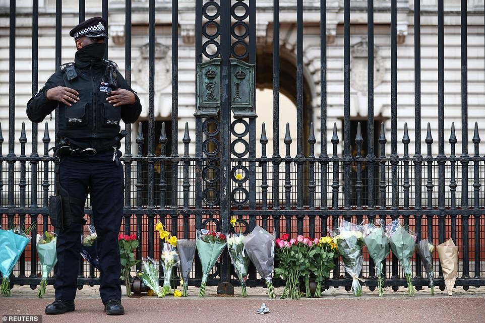 A police officer stands next to bouquets of flowers outside Buckingham Palace after the announcement on Friday at lunchtime