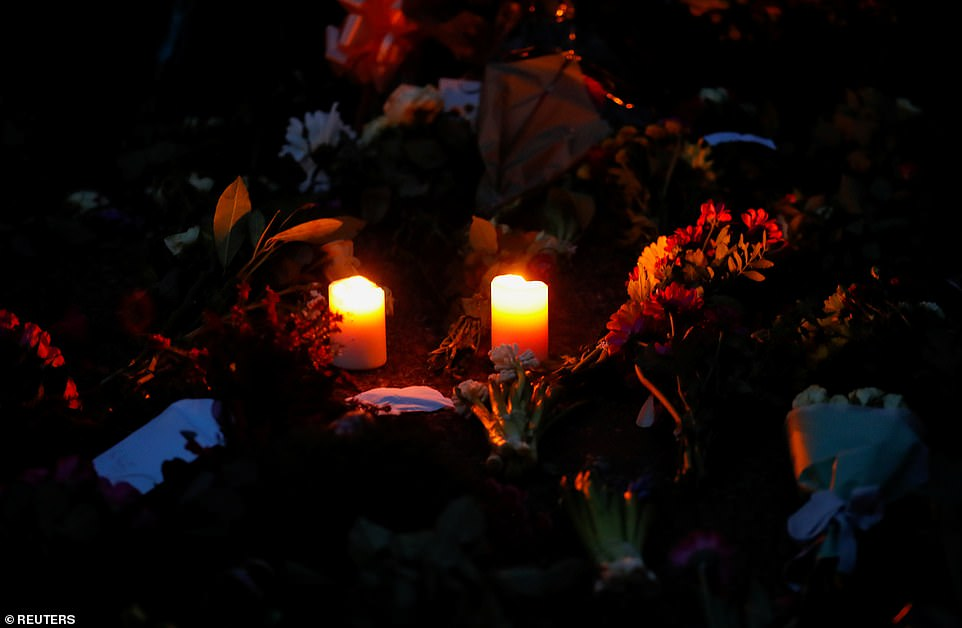 The tributes left by flocks of mourners were lit up by candlelight outsideWindsor Castle