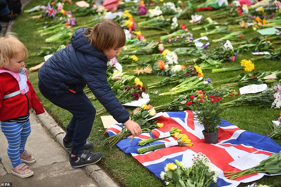 A young boy laid flowers at Cambridge Gate at Windsor Castle, Berkshire, following the announcement of the death of the Duke of Edinburgh