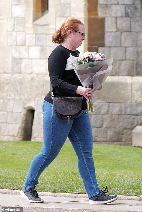 A woman takes flowers to the castle in Berkshire