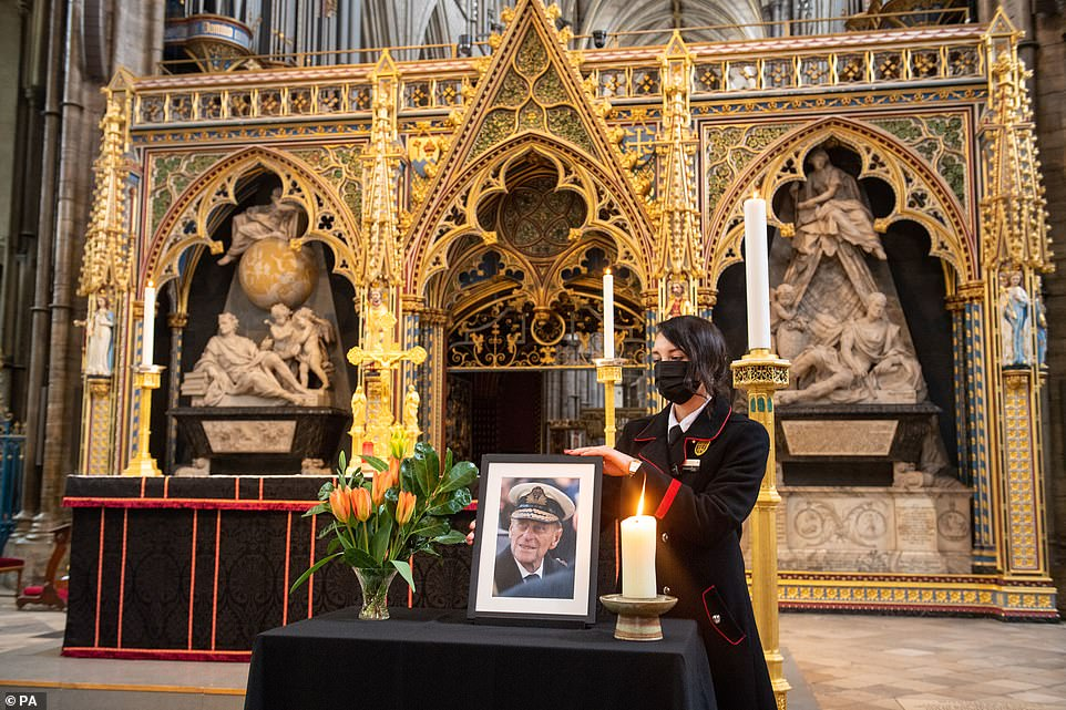 Rosa Wlodarczyk adjusts a photograph of the Duke of Edinburgh displayed alongside the nave at Westminster Abbey in London, which has been dressed in black to mark his death
