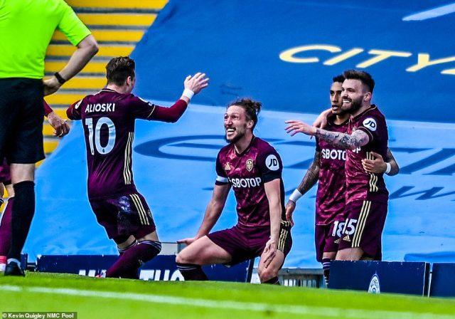 Leeds captain Luke Ayling celebrates withEzgjan Alioski while Brazilian attacker Raphinha congratulates the match winner