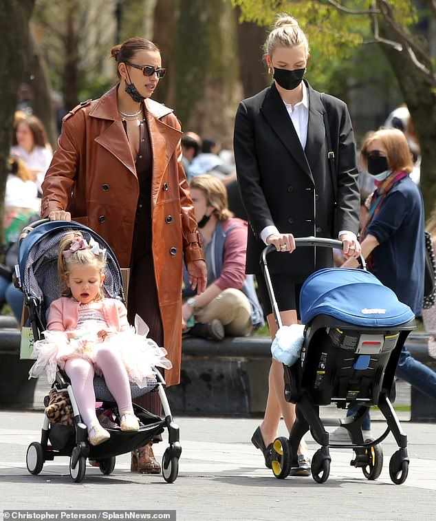 Loving parents: After enjoying the beautiful spring weather, the women put on their face masks and could be seen pushing their children around the house