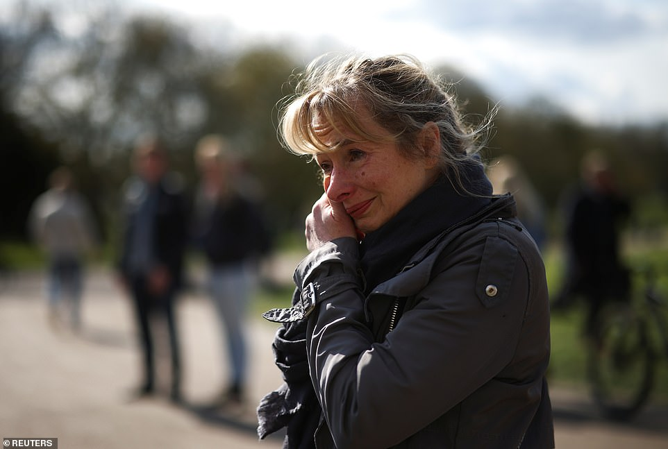 A mourner cries outside Windsor Castle this morning as the nation continues to pay tribute to the Duke of Edinburgh after his death