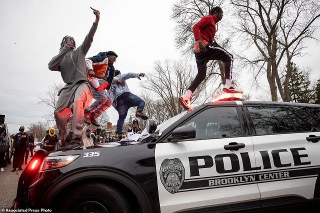 Men jump on police vehicles near the site of a shooting involving a police officer in Brooklyn Center, Minnesota