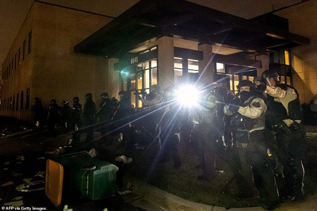 Police officers in riot gear fire tear gas in front of the Brooklyn Center Police Station as people gather to protest