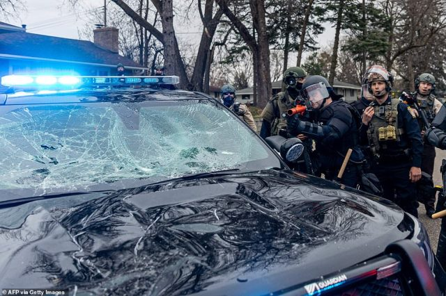 Police officers take cover as they clash with protesters after an officer reportedly shot and killed a black man in Brooklyn Center, Minneapolis, Minnesota. The incident involved a multi-car crash just prior to the officer discharging their weapon