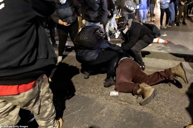 A demonstrator is helped by others after being injured by a tear-gas bomb in front of the Brooklyn Center Police Station