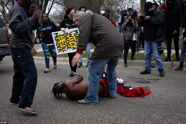 A man falls to the ground in agony after being shot by a rubber bullet as protesters clashed with police