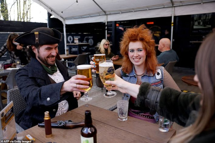 Customers, one dressed as a Pirate, enjoy a drink at the re-opened Village pub in northeast London