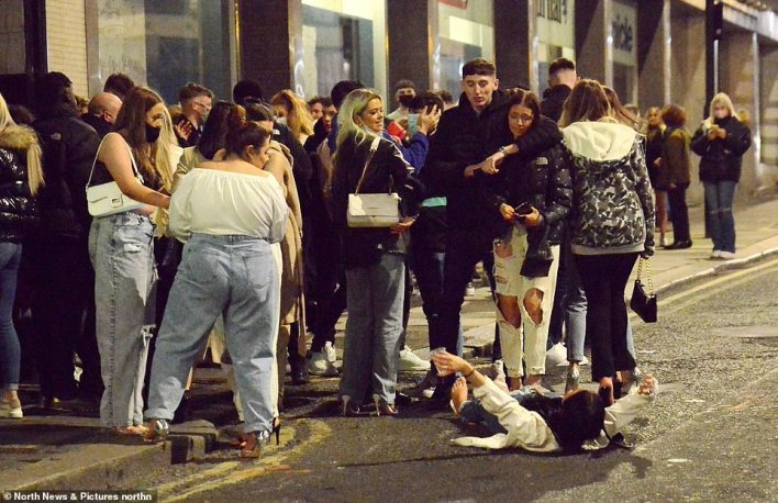 Crowds were seen gathered in Newcastle, where pictures show a raucous party-goer lying in the road with drink-in-hand as revellers watched on in surprise.