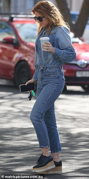 Stunning: The redheaded beauty wore her luscious tresses out, and her perfectly coiffed tresses bounced around her shoulders as she walked across the street with a coffee in one hand