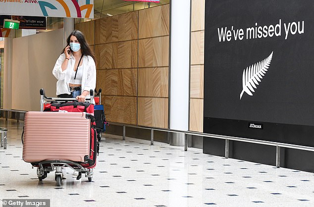 A passenger wearing a facemask arrives at Sydney's Kingsford Smith Airport from New Zealand (pictured) - the only country in the world Australians can travel to