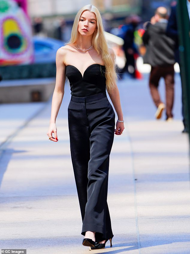 Black magic:The blonde beauty looked sensational in a black strapless top with a sweetheart neckline and matching high-waisted slacks as she walked past the city's skyscrapers