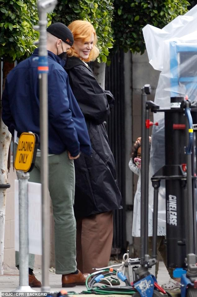On location: Kidman, 53, who wore a shoulder-length wig, wrapped warm on a cold Los Angeles day in a black hooded coat as she waited between takes