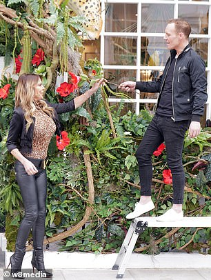 Why thanks!  Lizzie happily accepted a flower from a man working on the living room's impressive jungle-themed floral display