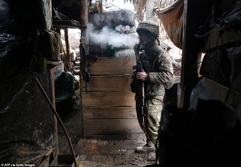 A Ukrainian soldier has a smoke break inside a trench in the Donetsk region close to the frontlines with Russian-backed separatists, where fighting has been ongoing for years