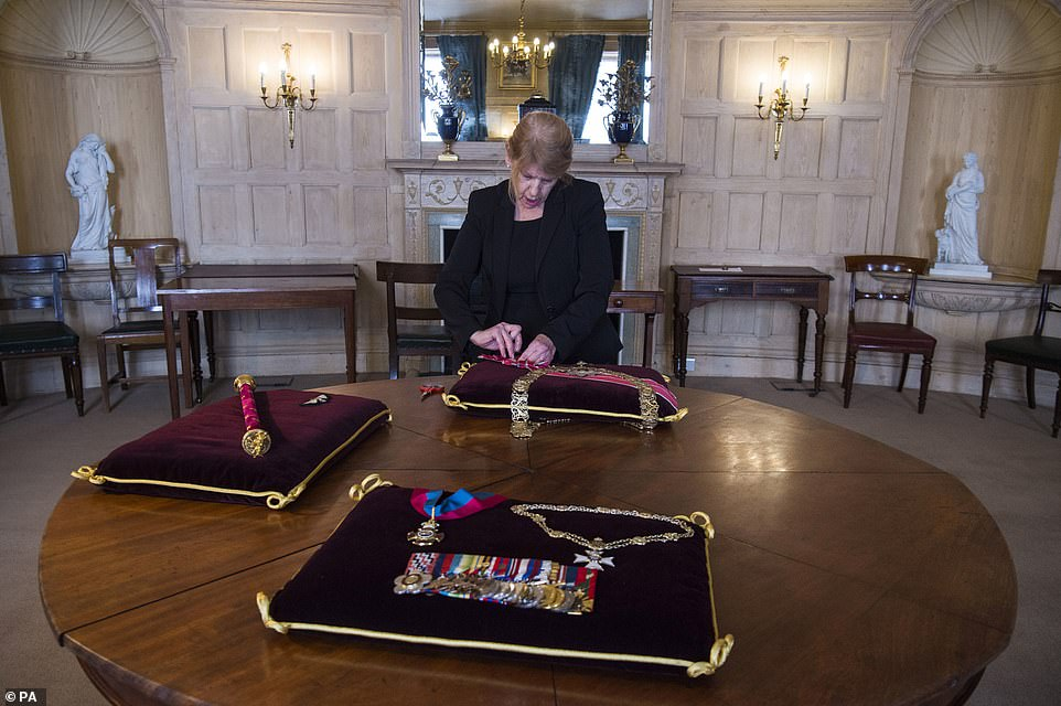 Diane Hatcher, a seamstress at Cleave Court Jewellers, sews medals and decorations conferred on Philip onto cushions today