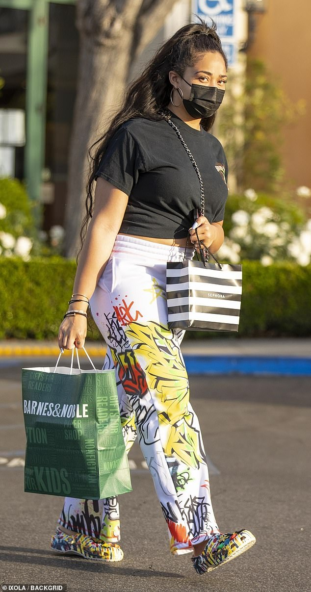 Funky: Jordyn Woods got in some retail therapy in Calabasas on Thursday, wearing a black t-shirt knotted above her navel and 'graffiti-covered' white pants with an elasticated waist