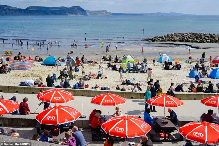 People flock to the beach at Lyme Regis in Dorset today, with the area busy with people enjoying the warm spring sunshine