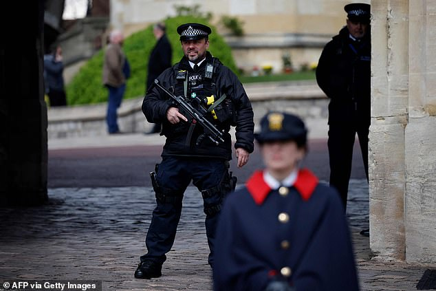 An armed policeman stands guard at the entrance to Windsor Castle