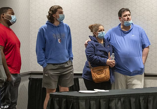 Family members await information about their loved ones who work at the FedEx facility in Indianapolis where a mass casualty shooting occurred late Thursday, early Friday, April 16, 2021