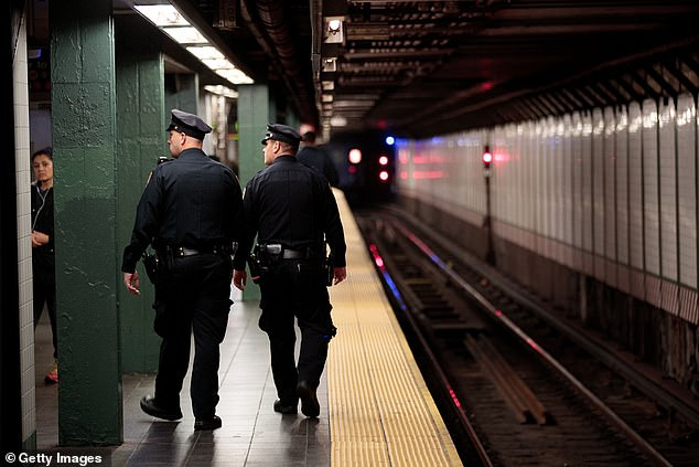 Police officers on the platform of Times Square subway station in New York, where a man was arrested with a gun and ammunition on Friday