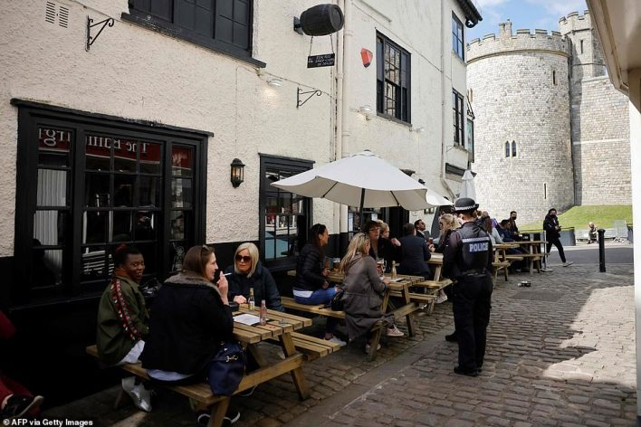 Customers enjoy a drink at a pub in the shadow of Windsor Castle this afternoon, one day before Prince Philip's funeral