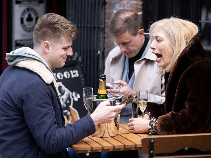 A group of people enjoy a drink while sat outside at a table in London's Soho this afternoon