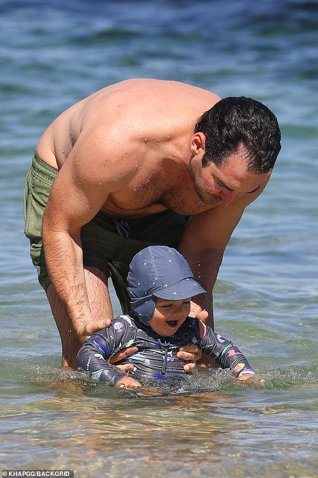 Beach boys: During their day, the enthusiastic dad held his son in his arms before placing his feet in the water playfully