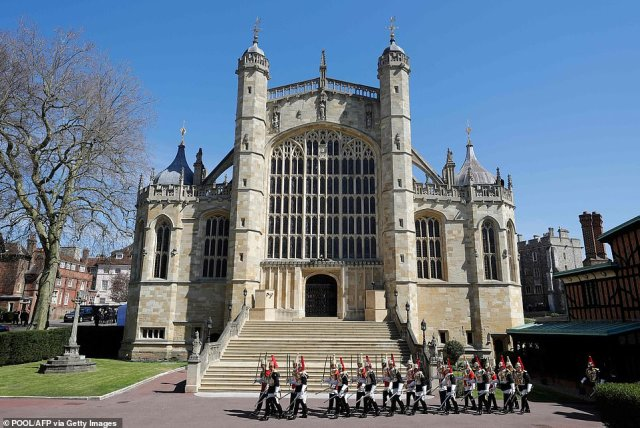 Members of the Household Cavalry march past St George's Chapel where Prince Philip's funeral is taking place