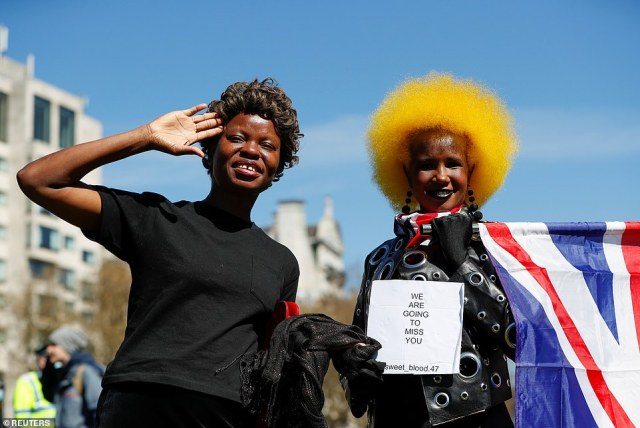 A woman salute as another holds a Union Jack flag at Wellington Arch in London on the day of the funeral of Prince Philip
