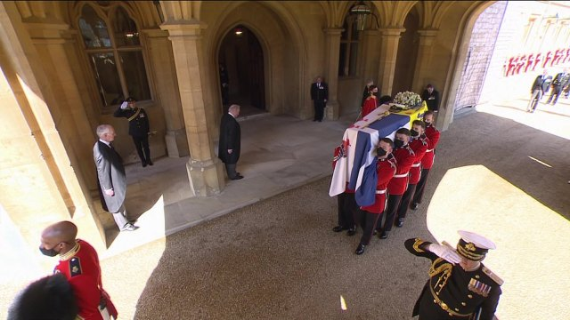 The Duke of Edinburgh's casket was covered in his personal standard and carried his sword, naval cap and a wreath of flowers as masked pallbearers lowered him on to his extraordinary self-designed Land Rover hearse